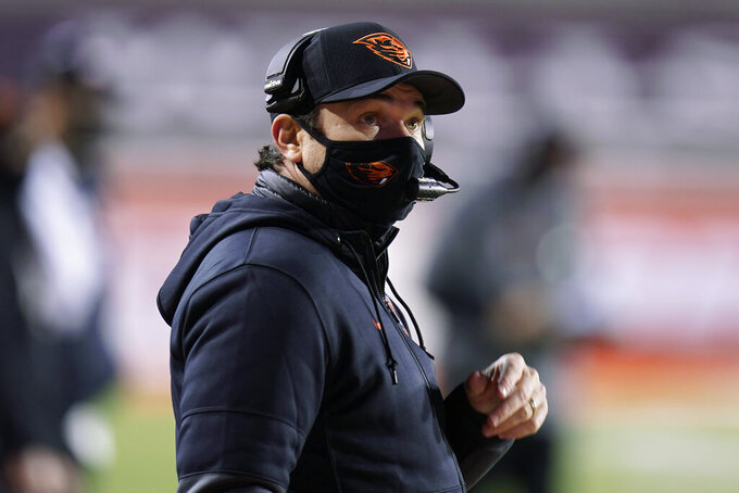 Oregon State coach Jonathan Smith looks at the scoreboard during the first half of the team's NCAA college football game against Utah on Saturday, Dec. 5, 2020, in Salt Lake City. (AP Photo/Rick Bowmer)