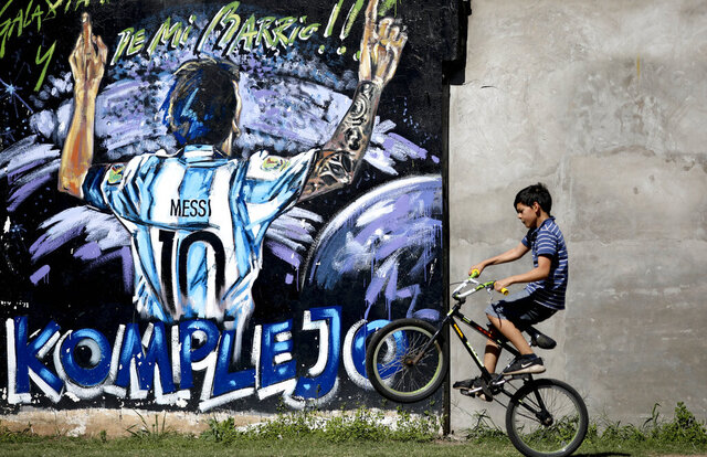 In this Dec. 5, 2019 photo, a boys pops a wheelie as he rides his bicycle past a mural featuring Lionel Messi in La Bajada, Rosario, Argentina. Soccer wasn't always Messi's favorite activity. When he was a child in the modest neighborhood of La Bajada in his hometown, he spent his time bicycling with friends, building forts out of branches and stones, playing hide and seek — and occasionally stealing lemons from a neighbor to make juice. (AP Photo/Natacha Pisarenko)