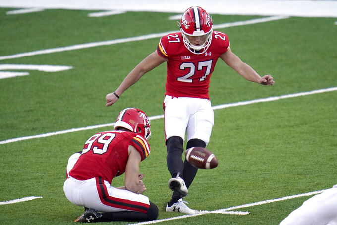 Maryland kicker Joseph Petrino, right, with Colton Spangler holding, misses a field goal against Rutgers during overtime of an NCAA college football game, Saturday, Dec. 12, 2020, in College Park, Md. Rutgers won 27-24 in overtime. (AP Photo/Julio Cortez)
