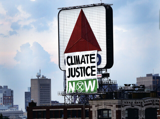 "Members of an environmental group hangs a banner that reads ""CLIMATE CHANGE NOW"" on the iconic Citgo sign near Boston's Fenway Park in Kenmore Square on Monday, Aug. 8, 2020 in Boston.  The group unfurled the banner Monday evening as the Red Sox began their game against the Tampa Bay Rays at Fenway. A spokesman for the group, Extinction Rebellion Boston, told The Boston Globe that it was hoping to bring attention to environmental issues. (Jim Davis/The Boston Globe via AP)"