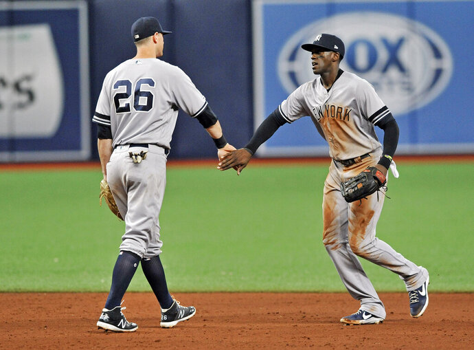 New York Yankees' DJ LeMahieu (26) and Cameron Maybin, right, celebrate the team's 4-3 win over the Tampa Bay Rays during the ninth inning of a baseball game Friday, May 10, 2019, in St. Petersburg, Fla. (AP Photo/Steve Nesius)