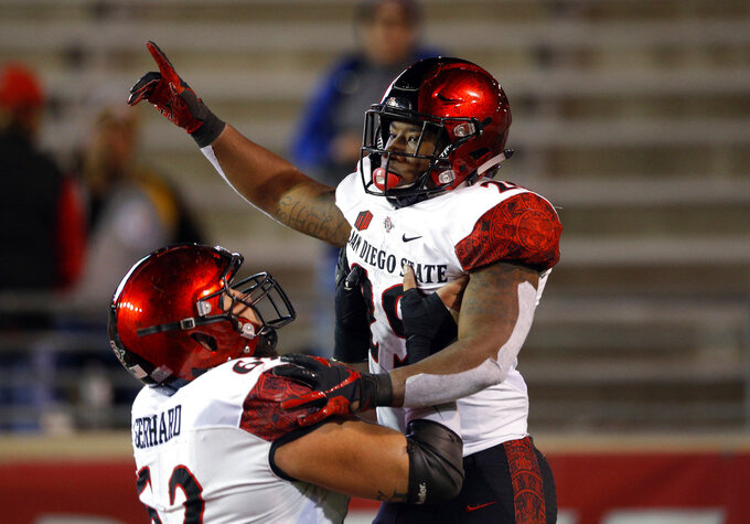 San Diego State running back Juwan Washington, right, celebrates with teammate Nick Gerhard after scoring a touchdown during the second half of an NCAA college football game in Albuquerque, N.M., Saturday, Nov. 3, 2018. San Diego State won 31-23. (AP Photo/Andres Leighton)