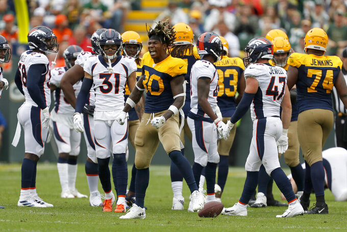 Green Bay Packers running back Jamaal Williams (30) celebrates after running for a first down and losing his helmet during the first half of an NFL football game against the Denver Broncos, Sunday, Sept. 22, 2019, in Green Bay, Wis. (AP Photo/Matt Ludtke)