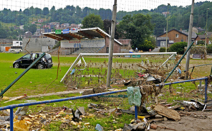 A damaged car and other debris are strewn across a soccer stadium playing field after flooding in Vaux-sous-Chevremont, Belgium, Saturday, July 24, 2021. Residents were still cleaning up after heavy rainfall hit the country causing flooding in several regions. (AP Photo/Virginia Mayo)
