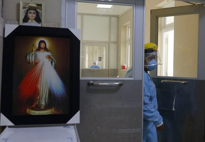A nurse enters a COVID-19 unit at the Honorio Delgado Hospital in Arequipa, Peru, Friday, June 25, 2021. Due to increased cases of COVID-19 and the Delta variant of the disease, the city is under a strict lockdown for 15 days beginning June 21. (AP Photo/Guadalupe Pardo)