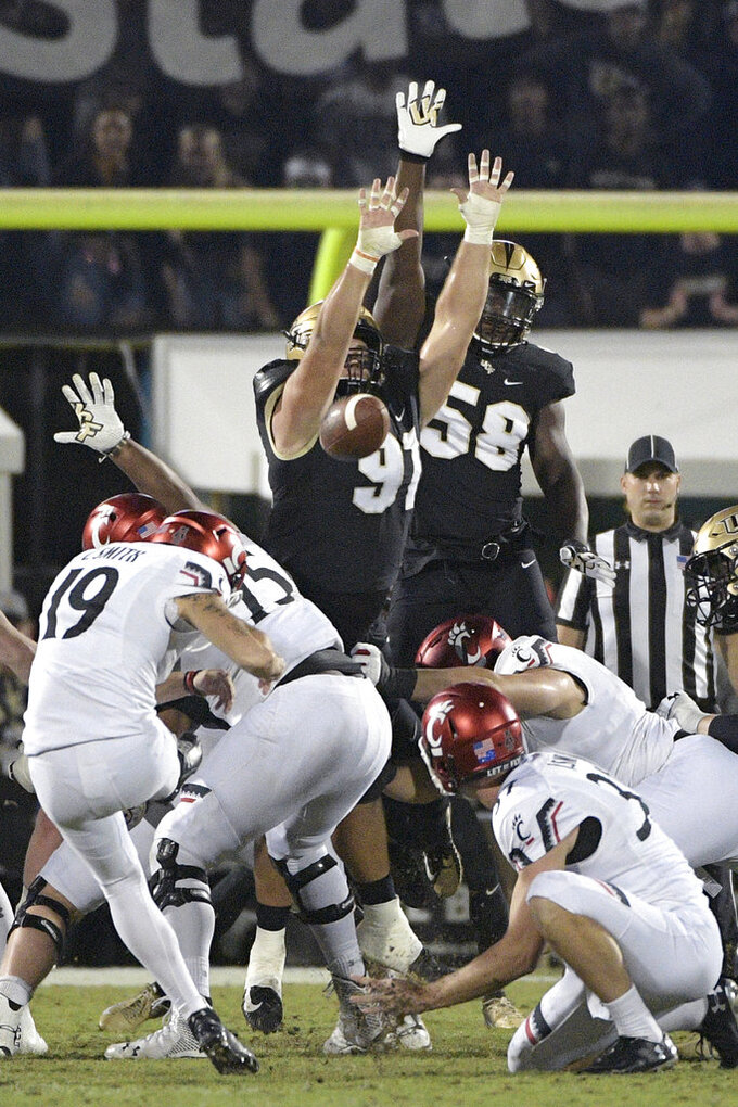 Central Florida defensive lineman Joey Connors (91) tries to block a 41-yard field goal attempt by Cincinnati place kicker Cole Smith (19) during the first half of an NCAA college football game Saturday, Nov. 17, 2018, in Orlando, Fla. (AP Photo/Phelan M. Ebenhack)