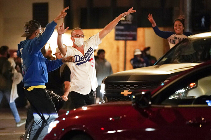 Baseball fans celebrate in downtown after the Los Angeles Dodgers won the World Series over the Tampa Bay Rays, Tuesday, Oct. 27, 2020, in Los Angeles. (AP Photo/Ashley Landis)