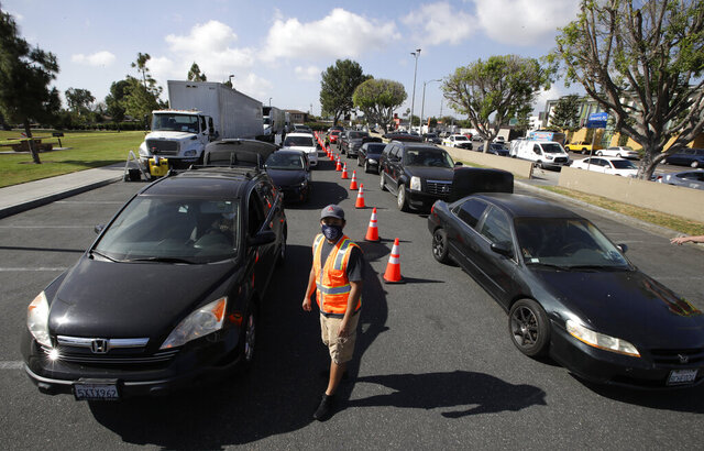 FILE - In this May 15, 2020, file photo, cars line up at a food distribution center in Compton, Calif. California lawmakers had harsh words Thursday, July 30, 2020, for the state agency that pays out unemployment, accusing its leaders of failing Californians who are waiting weeks or even months to receive their benefits. (AP Photo/Marcio Jose Sanchez, File)