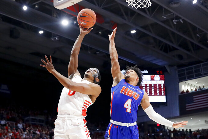 Dayton's Rodney Chatman (0) shoots against Houston Baptist's Myles Pierre (4) during the first half of an NCAA college basketball game, Tuesday, Dec. 3, 2019, in Dayton, Ohio. (AP Photo/John Minchillo)