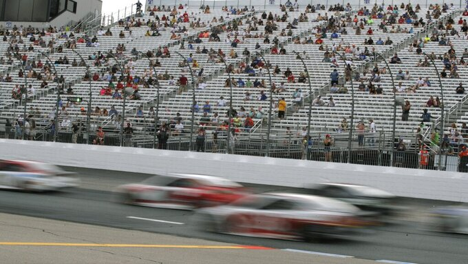 Cars streak past fans, sitting socially distanced, due to the coronavirus pandemic, in the grandstand during a NASCAR Cup Series auto race, Sunday, Aug. 2, 2020, at the New Hampshire Motor Speedway in Loudon, N.H. (AP Photo/Charles Krupa)