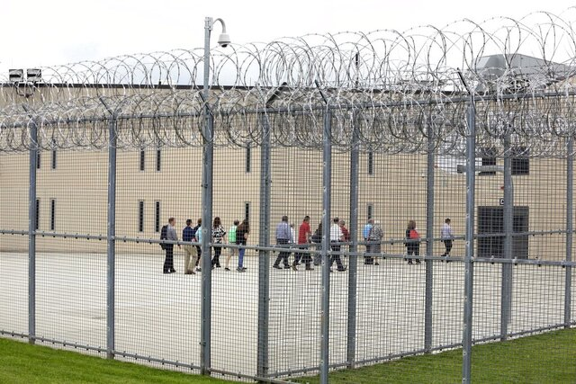 FILE - In this June 1, 2018, file photo, people walk on a tour of the West section of the State Correctional Institution at Phoenix in Collegeville, Pa. Pennsylvania Gov. Tom Wolf is issuing an executive order Friday, April 10, 2020, to authorize the early release of up to 1,800 inmates from Pennsylvania state prisons in an effort to minimize the spread of the new coronavirus. The Wolf administration has disclosed that 11 inmates at the State Correctional Institution-Phoenix, in Montgomery County outside Philadelphia, have contracted the virus. (AP Photo/Jacqueline Larma, File)