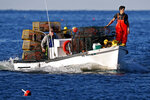 FILE - In this Saturday, Aug. 24, 2019, file photo, Adam Daggett stands lookout on the bow as his father, John Daggett, pilots their boat at Cape Porpoise in Kennebunkport, Maine. The state's harvest of lobsters is about 40 percent off last year's pace through September. The state's fishermen are in jeopardy of bringing less than 100 million pounds of lobster to the docks for the first time since 2010. (AP Photo/Robert F. Bukaty, File)