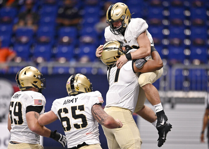 Army quarterback Cade Ballard, right, celebrates a touchdown with teammates Jordyn Law, Noah Knapp (65) and Mike Johnson (59) during an NCAA college football game against UTSA on Saturday, Oct. 17, 2020, in San Antonio, Texas. Army won 28-16. (AP Photo/Darren Abate)