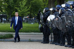 FILE - In this Monday, June 1, 2020, file photo, President Donald Trump walks past police in Lafayette Park after visiting outside St. John's Church across from the White House in Washington. Part of the church was set on fire during protests on Sunday night. (AP Photo/Patrick Semansky, File)