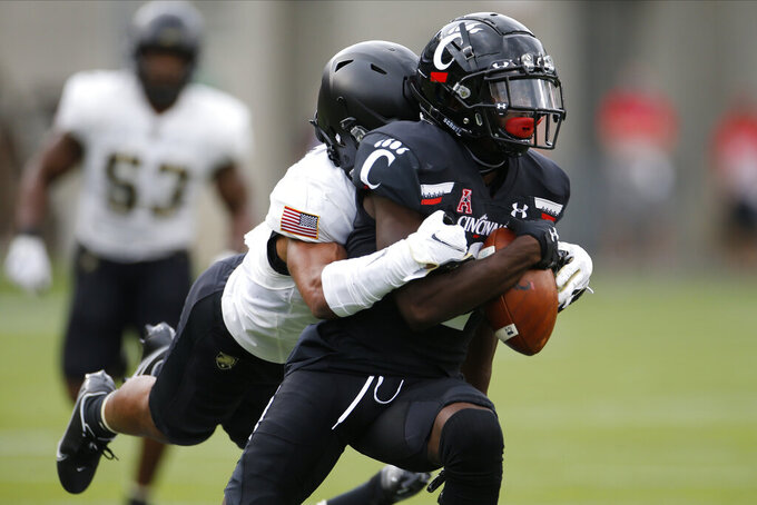 Army defensive back Javhari Bourdeau, left, tackles Cincinnati wide receiver Jayshon Jackson after a catch during the first half of an NCAA college football game Saturday, Sept. 26, 2020, in Cincinnati, Ohio. (AP Photo/Jay LaPrete)