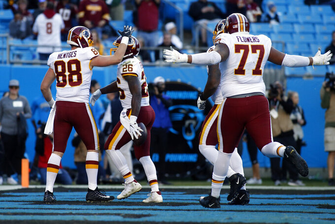 Washington Redskins tight end Hale Hentges (88) and offensive guard Ereck Flowers (77) celebrate with running back Adrian Peterson (26) following Peterson's touchdown against the Carolina Panthers during the second half of an NFL football game in Charlotte, N.C., Sunday, Dec. 1, 2019. (AP Photo/Brian Blanco)
