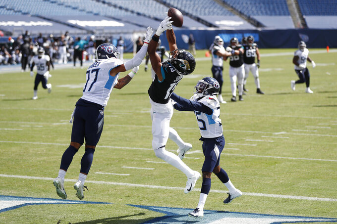 Jacksonville Jaguars wide receiver Collin Johnson (19) reaches for a pass between Tennessee Titans defenders Tennessee Titans safety Amani Hooker (37) and defensive back Chris Jackson (35) in the first half of an NFL football game Sunday, Sept. 20, 2020, in Nashville, Tenn. The pass was incomplete. (AP Photo/Wade Payne)