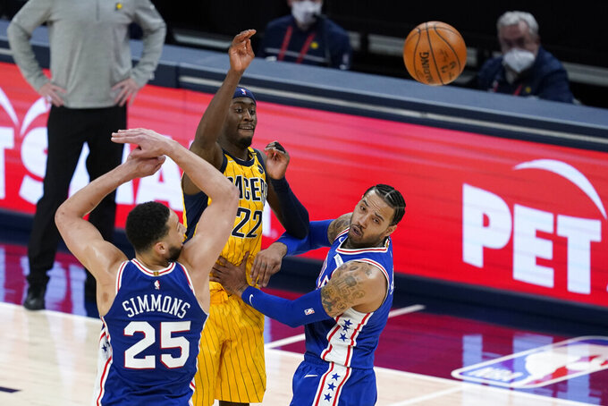 Indiana Pacers' Caris LeVert (22) makes a pass against Philadelphia 76ers' Ben Simmons (25) and Mike Scott during the second half of an NBA basketball game, Tuesday, May 11, 2021, in Indianapolis. Indiana won 103-94. (AP Photo/Darron Cummings)