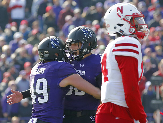 Northwestern's Drew Luckenbaugh, center, celebrates his game-winning field goal in overtime with teammate Jake Collins, left, next to Nebraska's Tre Neal in an NCAA college football game Saturday, Oct. 13, 2018, in Evanston, Ill.. (AP Photo/Jim Young)