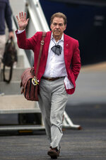 Alabama NCAA college football head coach Nick Saban waves as he walks toward cheering fans as the University of Alabama football team arrives home at the Tuscaloosa National Airport after winning the 2021 College Football Playoff national championship, Tuesday, Jan. 12, 2021, in Tuscaloosa, Ala. (AP Photo/Vasha Hunt)