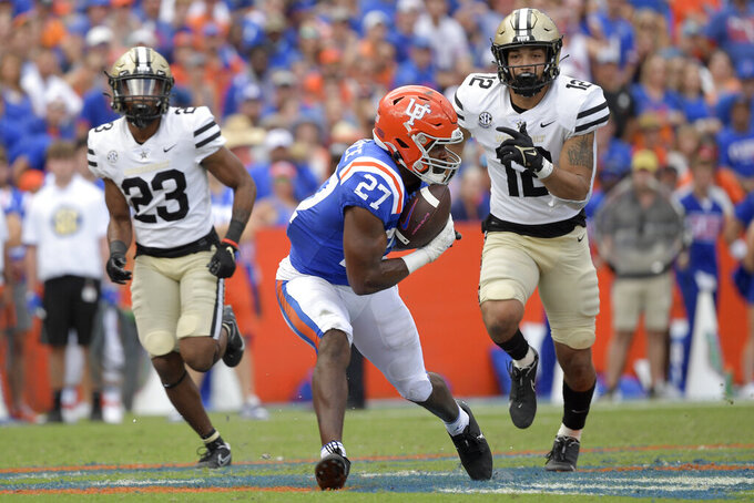 Florida running back Dameon Pierce (27) catches a pass in front of Vanderbilt cornerback Jaylen Mahoney (23) and linebacker Brayden DeVault-Smith (12) for a 61-yard touchdown play during the second half of an NCAA college football game, Saturday, Oct. 9, 2021, in Gainesville, Fla. (AP Photo/Phelan M. Ebenhack)
