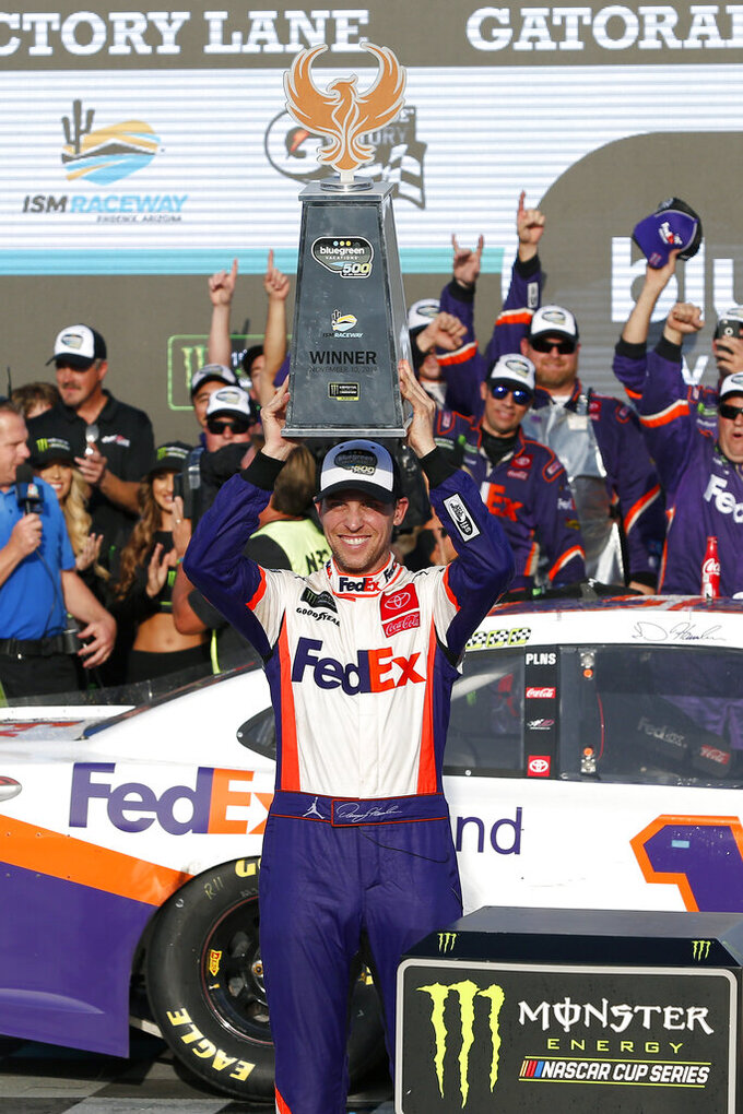 Denny Hamlin holds up the trophy after winning the NASCAR Cup Series auto race Sunday, Nov. 10, 2019, in Avondale, Ariz. (AP Photo/Ralph Freso)