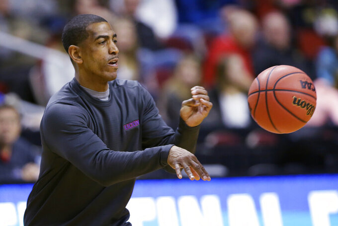 FILE - In this March 16, 2016, file photo, Connecticut coach Kevin Ollie passes the ball during practice for the team's first-round game in the NCAA men's college basketball tournament in Des Moines, Iowa.  Former UConn basketball coach Ollie has brought his $10 million dispute with the school over his firing to both state and federal court. Lawyers for Ollie and the university were to give oral arguments Friday, Jan. 25, in U.S. District Court in Bridgeport on a motion that would allow Ollie to move forward with a racial discrimination complaint against the school without jeopardizing his right to an arbitration hearing with UConn over his firing last year. (AP Photo/Charlie Neibergall, File)