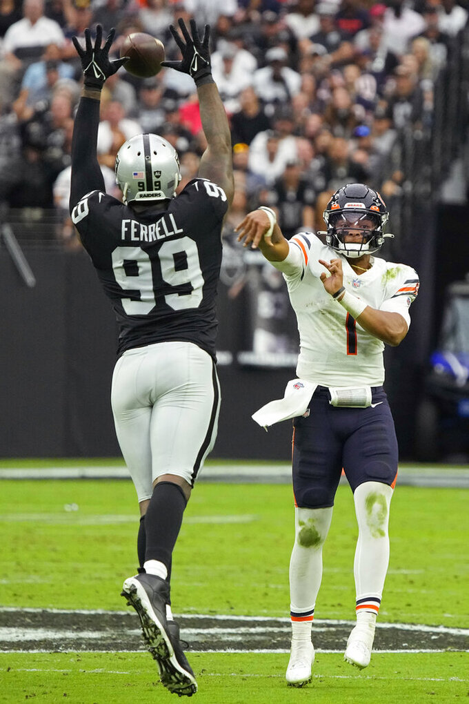 Las Vegas Raiders defensive end Clelin Ferrell (99) attempts to block a pass by Chicago Bears quarterback Justin Fields (1) during the first half of an NFL football game, Sunday, Oct. 10, 2021, in Las Vegas. (AP Photo/Rick Scuteri)