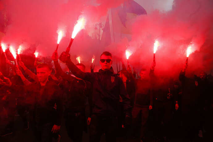 Members of the nationalist movements light flares during a rally marking Defense of the Homeland Day in center Kyiv, Ukraine, Monday, Oct. 14, 2019. Some 15,000 far-right and nationalist activists protested in the Ukrainian capital, chanting