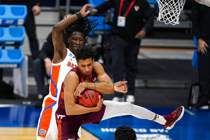 Virginia Tech Hokies forward Keve Aluma (22) grabs a rebound in front of Florida forward Anthony Duruji (4) in the first half of a first round game in the NCAA men's college basketball tournament at Hinkle Fieldhouse in Indianapolis, Friday, March 19, 2021. (AP Photo/Michael Conroy)