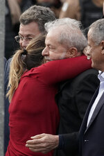 Brazil's former President Luiz Inacio Lula da Silva gets a hug from his daughter Lurian Cordeiro da Silva as he exits the the Federal Police headquarters where he was imprisoned on corruption charges in Curitiba, Brazil, Friday, Nov. 8, 2019. Da Silva walked out of prison less than a day after the Supreme Court ruled that a person can be imprisoned only after all the appeals have been exhausted. (AP Photo/Leo Correa)