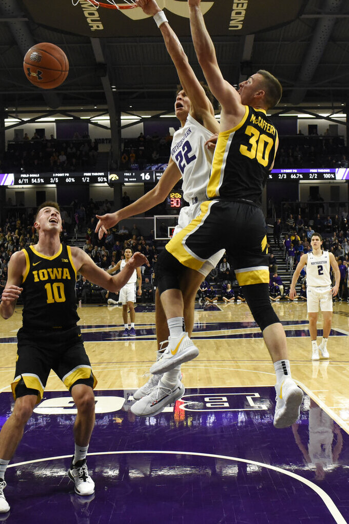 Northwestern forward Pete Nance (22) dunks next to  Iowa guard Connor McCaffery (30) during the first half of an NCAA college basketball game Tuesday, Jan. 14, 2020, in Evanston, Ill. (AP Photo/David Banks)