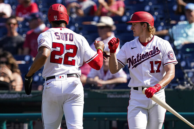 Washington Nationals' Juan Soto celebrates with Andrew Stevenson after he was walked home during the fifth inning of a baseball game against the Miami Marlins at Nationals Park, Wednesday, Sept. 15, 2021, in Washington. (AP Photo/Alex Brandon)