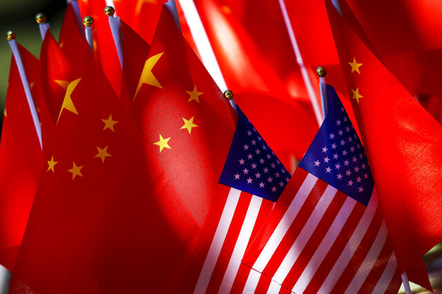 FILE - In this Sept. 16, 2018, file photo, American flags are displayed together with Chinese flags on top of a trishaw in Beijing. China's economy czar will visit Washington next week for the signing of an interim trade deal, the government said Thursday, Jan. 9, 2020. (AP Photo/Andy Wong, File)