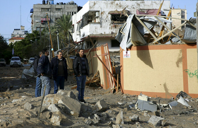 Palestinians inspect the damage of the offices of Hamas leader Ismail Haniyeh, in Gaza City, Tuesday, March 26, 2019. A tense quiet took hold Tuesday morning after a night of heavy fire as Israeli aircraft bombed targets across the Gaza Strip and Gaza militants fired rockets into Israel in what threatened to devolve into a major conflict two weeks before the Israeli election. (AP Photo/Adel Hana)