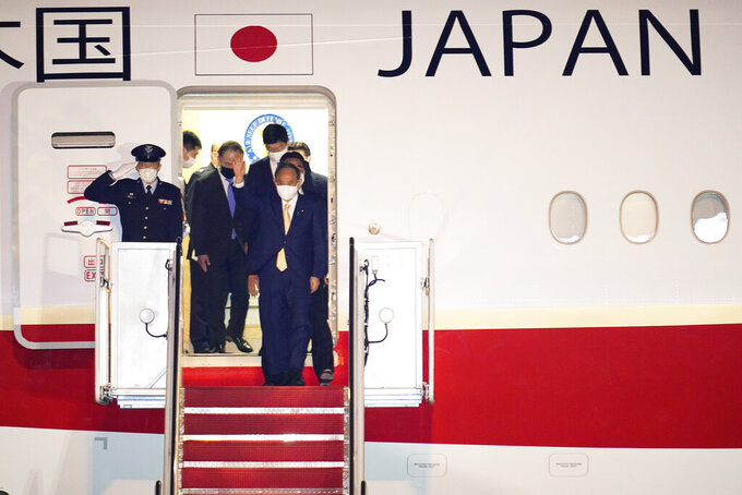 Japanese Prime Minister Yoshihide Suga arrives at Andrews Air Force Base, Md., Thursday, April 15, 2021. Suga will be the first foreign leader to have a face-to-face meeting with President Joe Biden, when they meet at the White House on Friday. (AP Photo/Manuel Balce Ceneta)