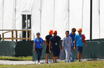 FILE - In this Monday, May 6, 2019 file photo, migrant children walk outside the Homestead Temporary Shelter for Unaccompanied Children in Homestead, Fla. The U.S. government is providing long-distance video counseling to teens housed at the country's largest migrant detention center as officials struggle to accommodate increasing numbers of minors illegally crossing the U.S.-Mexico border. Some mental health experts and human rights advocates say that may not be the best way to help young people coping with trauma. (AP Photo/Wilfredo Lee, File)