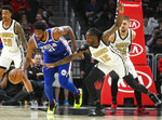 Philadelphia 76ers center Joel Embiid (21) tries to fend off the defense of Atlanta Hawks forward Taurean Prince (12) during the first half of an NBA basketball game Saturday, March 23, 2019, in Atlanta. (AP Photo/John Amis)