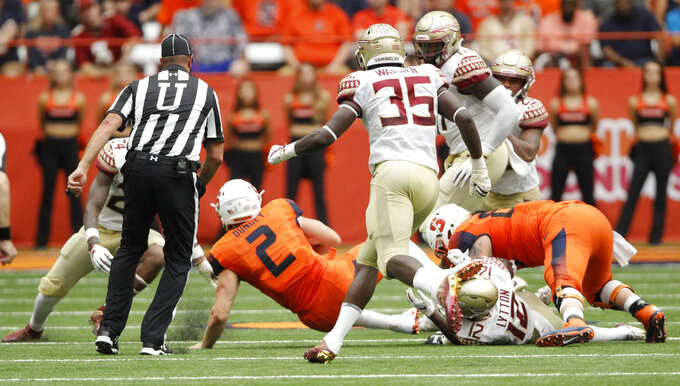 Syracuse's Eric Dungey, center, is tackled in the second quarter of an NCAA college football game against Florida State in Syracuse, N.Y., Saturday, Sept. 15, 2018. Dungey did not reenter the game after the play. Syracuse won 30-7. (AP Photo/Nick Lisi)