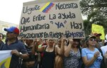 FILE - In this Feb. 12, 2019 file photo, Venezuelans living in Colombia protest the government of Venezuela's President Nicolas Maduro, and its blocking the entry of humanitarian aid, in Cucuta, Colombia, on the border with Venezuela. The sign reads in Spanish