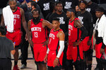 Houston Rockets' P.J. Tucker, from left, James Harden (13), Russell Westbrook (0), Robert Covington (33) and others look up at a video board to watcha replay during the second half of an NBA first-round playoff basketball game against the Oklahoma City Thunder on Monday, Aug. 31, 2020, in Lake Buena Vista, Fla. (AP Photo/Mark J. Terrill)