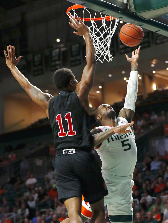 Miami guard Zach Johnson (5) goes up for a shot against North Carolina State guard Markell Johnson (11) during the first half of an NCAA college basketball game, Thursday, Jan. 3, 2019, in Coral Gables, Fla. (AP Photo/Wilfredo Lee)