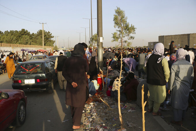 Hundreds of people gather near an evacuation control checkpoint during ongoing evacuations at Hamid Karzai International Airport, in Kabul, Afghanistan, Wednesday, Aug. 25, 2021. The Taliban wrested back control of Afghanistan nearly 20 years after they were ousted in a U.S.-led invasion following the 9/11 attacks. Their return to power has pushed many Afghans to flee, fearing reprisals from the fighters or a return to the brutal rule they imposed when they last ran the country. (AP Photo)