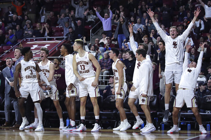 Boston College guard Jared Hamilton (3) celebrates with teammates after hitting a 3-pointer against Virginia during late in the second half of an NCAA college basketball game Tuesday, Jan. 7, 2020 in Boston. Boston College upset Virginia 60-53. (AP Photo/Charles Krupa)