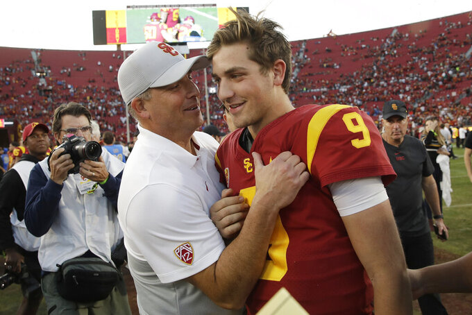 FILE - In this Nov. 23, 2019, file photo, Southern California head coach Clay Helton, left, smiles at quarterback Kedon Slovis (9) after a 52-35 win over UCLA in an NCAA college football game, in Los Angeles. Slovis was selected as The Associated Press Pac 12 Conference team Newcomer of the Year, Thursday, Dec. 12, 2019. (AP Photo/Marcio Jose Sanchez, File)