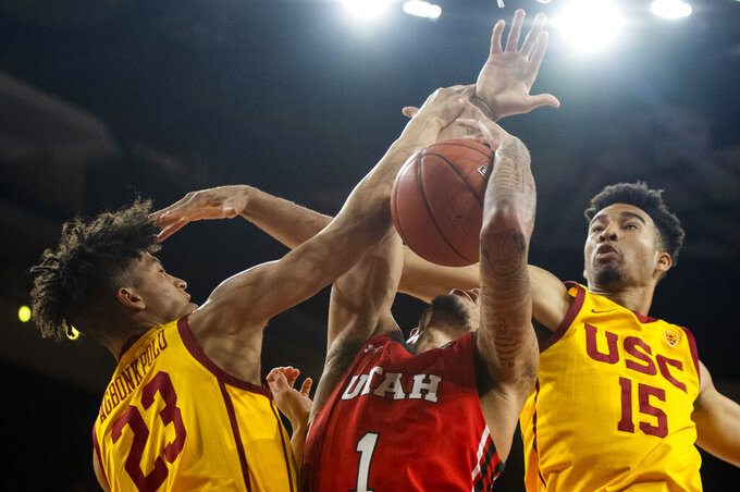 Southern California forward Max Agbonkpolo, left, fouls Utah forward Timmy Allen, center, during the second half of an NCAA college basketball game Thursday, Jan. 30, 2020 in Los Angeles. (AP Photo/Kyusung Gong)