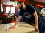Blue Owl Restaurant employee Will DeVinney sanitizes a table in Kimmswick, Mo., on Sunday, Oct. 18, 2020. Businesses are receiving large support from the community after being hit by COVID-19 as well as the cancellation of the annual Apple Butter Festival.  (Christine Tannous /St. Louis Post-Dispatch via AP)
