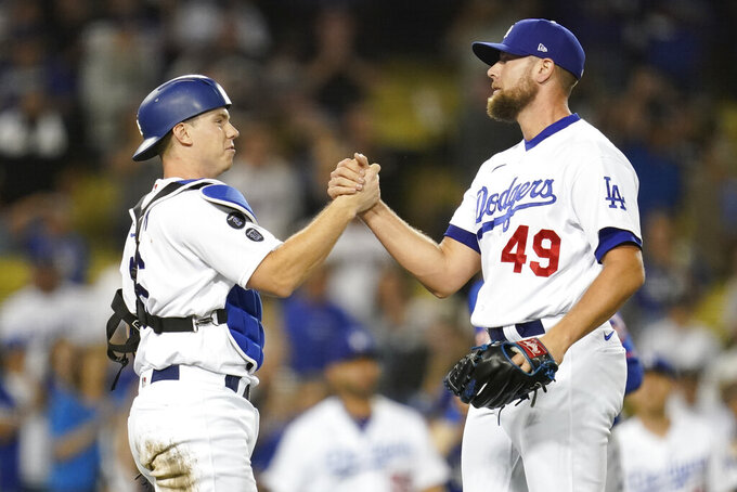 Los Angeles Dodgers catcher Will Smith, left, and relief pitcher Blake Treinen (49) celebrate after a 4-1 win over the New York Mets in their baseball game Thursday, Aug 19, 2021, in Los Angeles. (AP Photo/Ashley Landis)