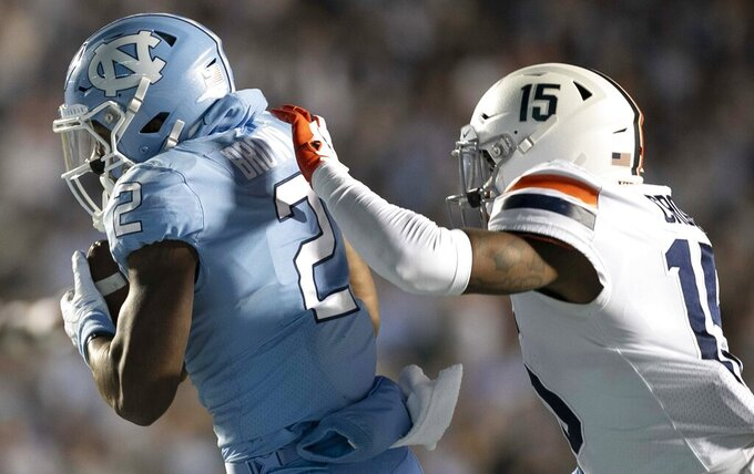North Carolina's Dyami Brown (2) pulls in a 34-yard pass from quarterback Sam Howell for a touchdown ahead of Virginia's De'Vante Cross during the second quarter of an NCAA college football game Saturday, Nov. 2, 2019, in Chapel Hill, N.C. (Robert Willett/The News & Observer via AP)