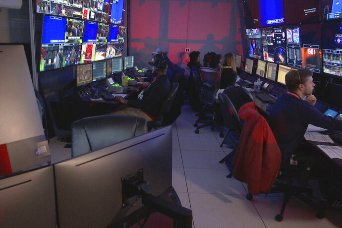 In this Thursday, Nov. 7, 2019, photo taken from video, technicians monitor video feed from 38 cameras placed around State Farm Arena in Atlanta in order to produce 3 dimensional video replays. The Atlanta Hawks Friday will become the fifth NBA team to unveil significant financial investments into new 360-degree replay technology designed to eventually give fans the power to change the way they see the game.  (AP Photo/Cody Jackson)